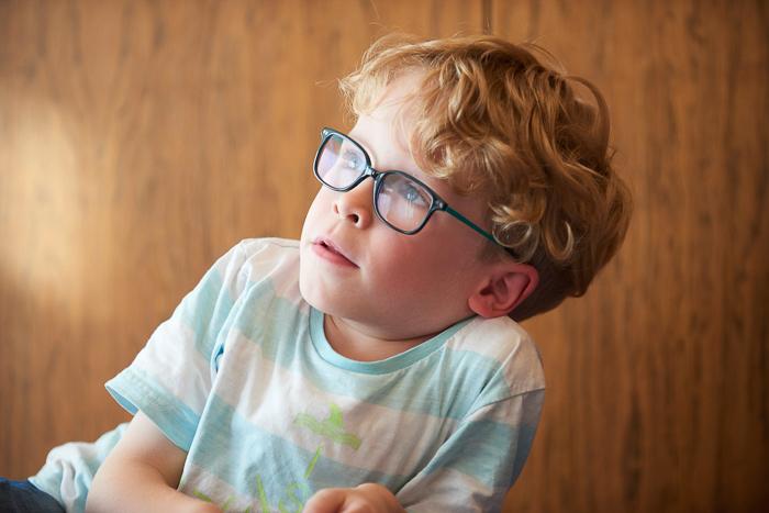 Kind mit Brille schaut nach links oben